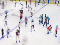 Defocused of indoor ice skating park with skating people.